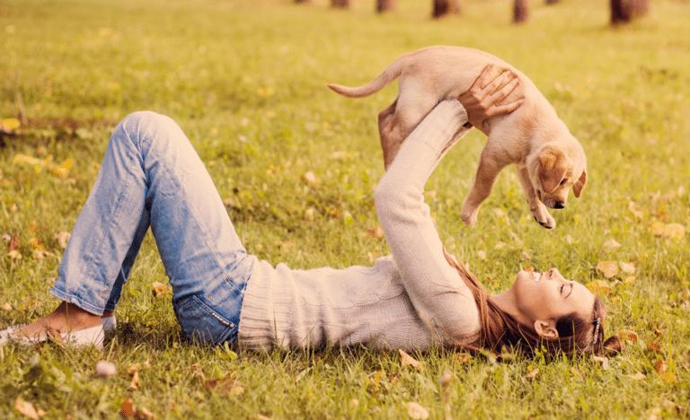 Femeie jucându-se cu un pui de cățel în iarbă.