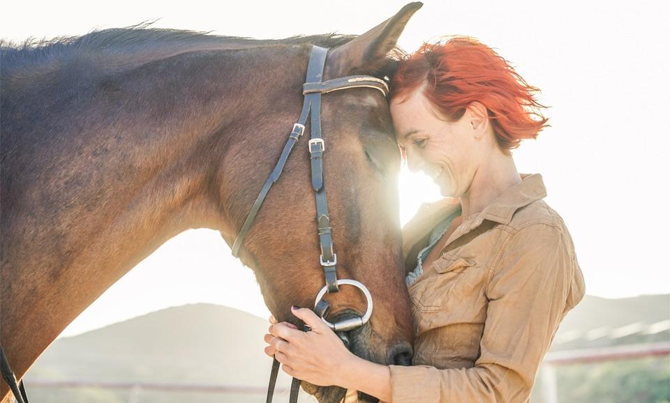 Fata roscata imbratisand un cal.