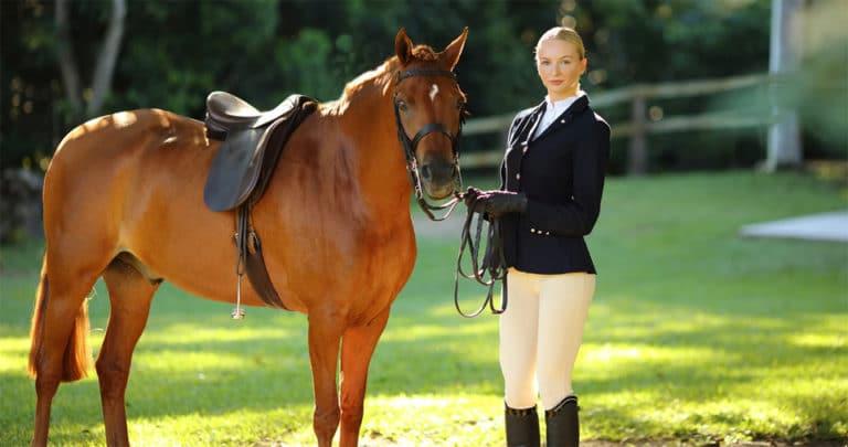 Femeie blonda stand langa un cal.