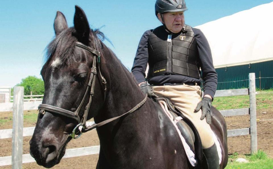 Barbat in varsta calarind un cal negru.